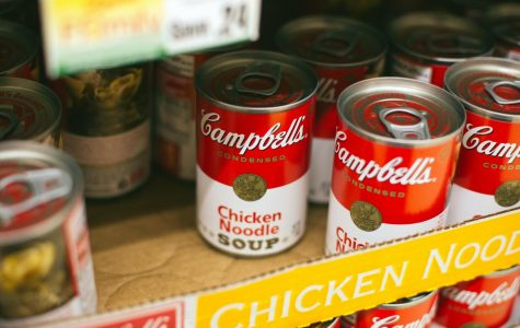 A photo of soup cans on cardboard. Many in the community are struggling to get essential supplies such as food in the current COVID-19 crisis. The local food bank has been working to ease this struggle.