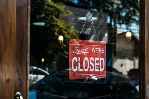 A sign hangs from a shop window, notifying customers that it is closed. Due to COVID-19, many governors had issued stay-at-home orders and shut down non-essential businesses. However, many states are seeking to open early, a dangerous move since the virus is still spreading rapidly and hospitals are ill-equipped to deal with the amount of people infected.