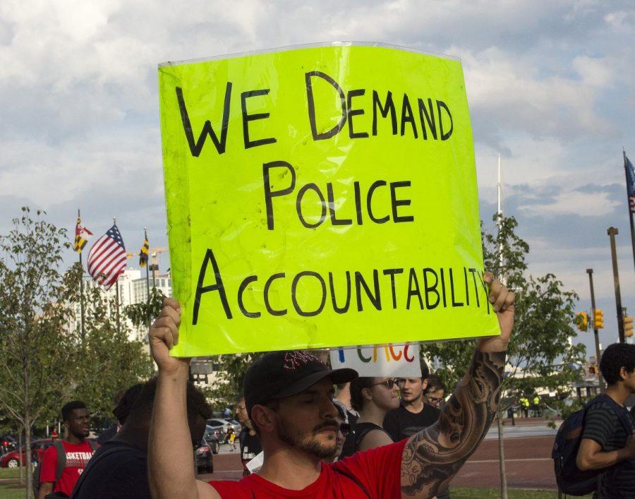 Black Lives Matter protestors gather around to demand justice against police brutality.