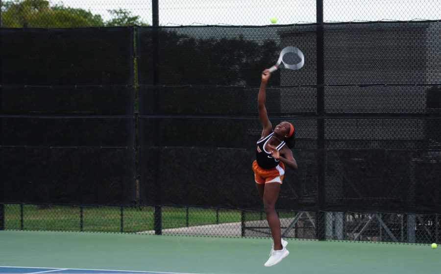 "While mid-air, Kinaa Graham '23 hits a strong serve in her singles match. The Warriors won all but one match against Vandegrift. ""The first couple matches of the season are always mostly about getting back into the team environment and bonding with the new players,"" Graham said."