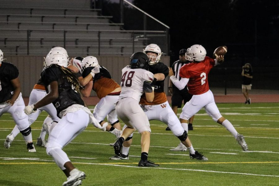 Quarterback RJ Martinez '21 throws the ball to a receiver while teammates help block opponents. The pass fell incomplete, and the Warriors prepared for the next play.