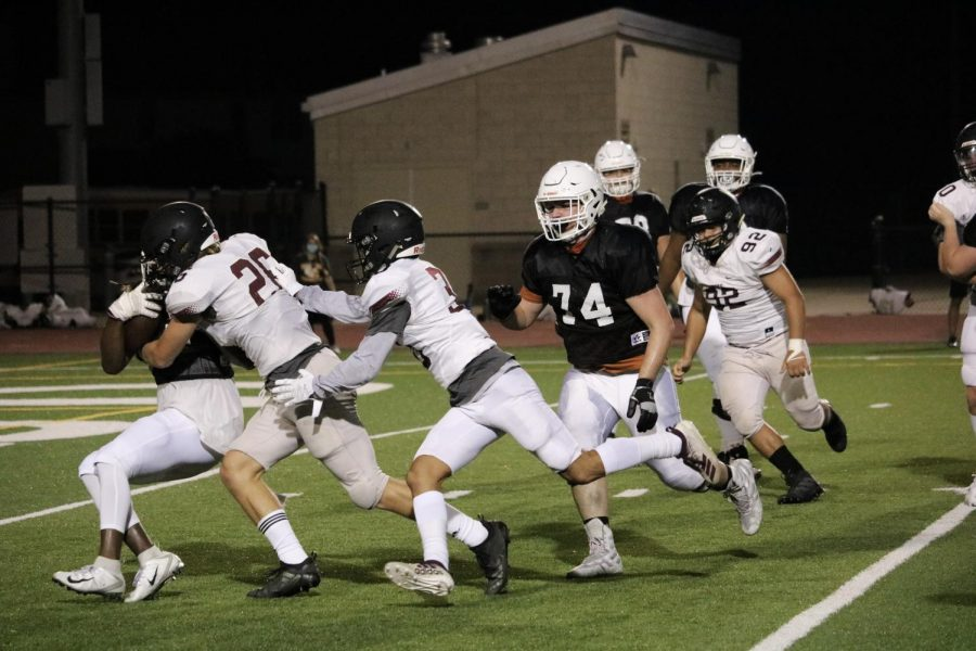 While running the ball down, Nate Anderson '21 gets tackled by the Raiders' defense. He later was able to score a touchdown for the Warriors.