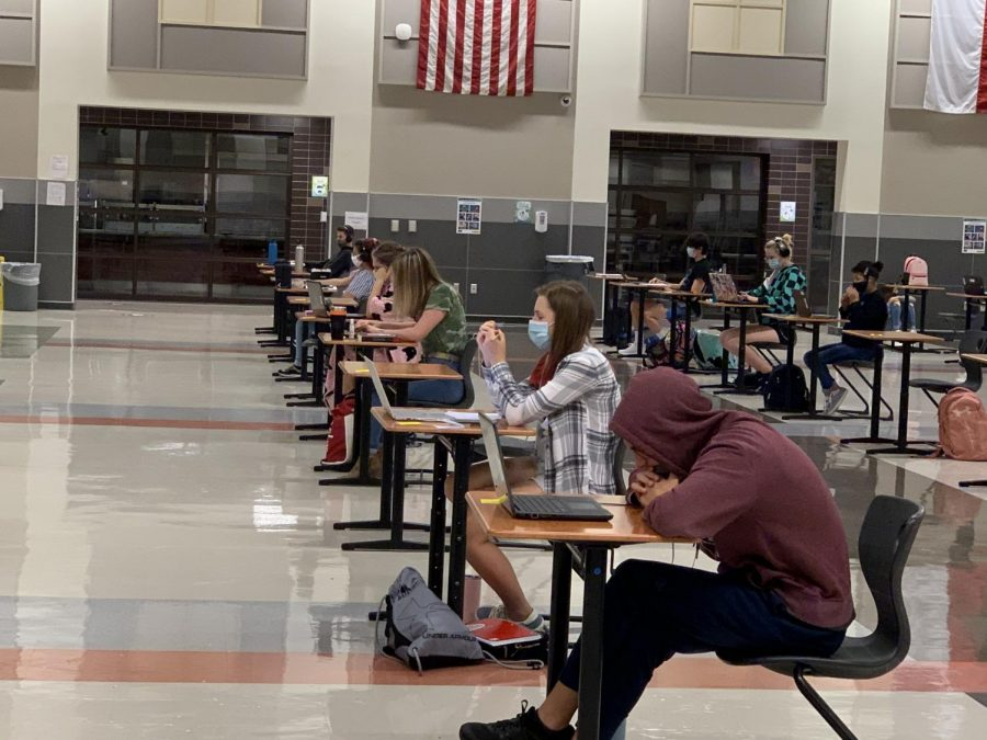 Students who have chosen to return to campus sit at desks appropriately distanced from each other.