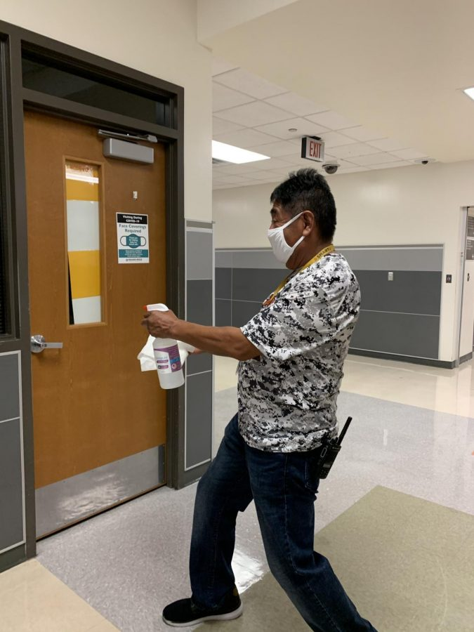 Lead custodian Mr. Eddy Moreno uses district provided Ionopure disinfecting solution to sanitize a door handle and other frequently touched surfaces.