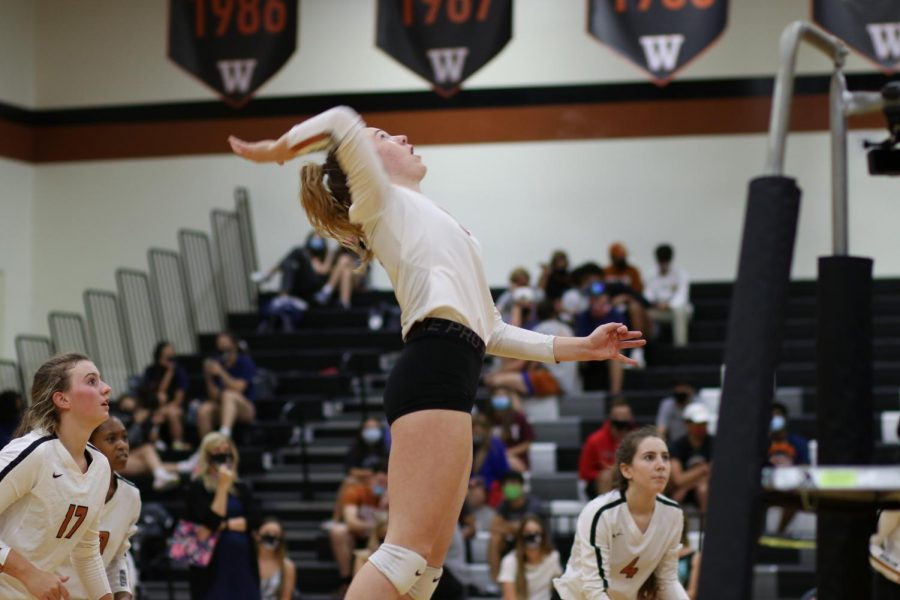 Looking up, Erin Fagan '22 prepares to spike the ball against Hutto. The Lady Warriors swept their rivals to propel them into the postseason, where they eventually fell to Madison in the second round.