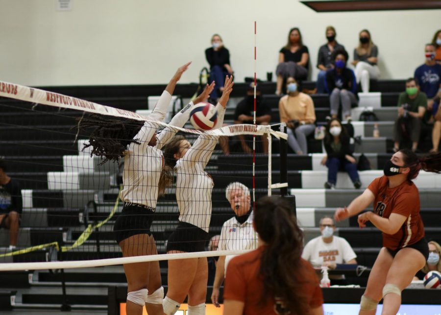 Jumping up, Trinity Woods '23 and Abby Gregorczyk '21 block the ball against Hutto. The Lady Warriors rode a strong end to the regular season to a dominant opening-round victory over Austin.