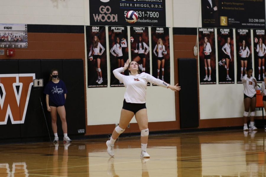 Winding up, Lauren Kelley '21 prepares to serve the ball. Despite their best efforts, the Warriors ended up giving the point to Hutto during this play.