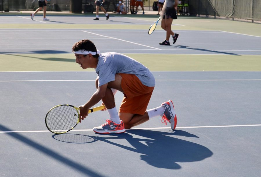 """Zeyad Elchouemi '22 crouches in eye-formation, focused on his opponents as his partner Sachchit Sivaram '21 serves from the baseline. The classic doubles team would go on to win 6-1, 6-1. """"I think it's good that we're playing team tennis again [because] not every sport is lucky enough to be playing and I think the team has what it takes to get that state title hopefully,"""" Elchouemi said."""