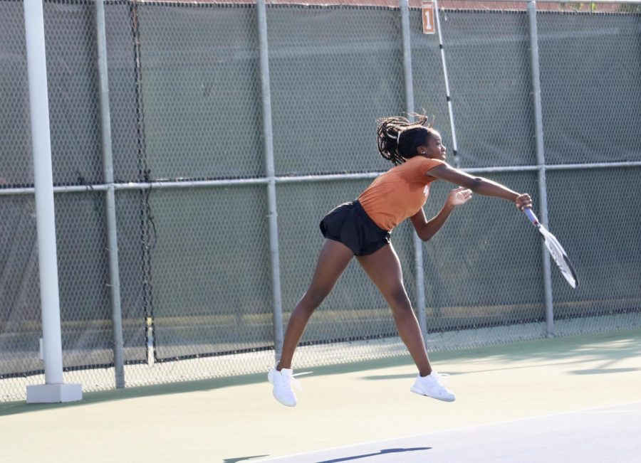 Kinaa Graham '23 jumps forward on her serve, reaching out and following through. Graham and her doubles partner Simryn Jacob '24 would go on to win their match 6-1, 6-1.