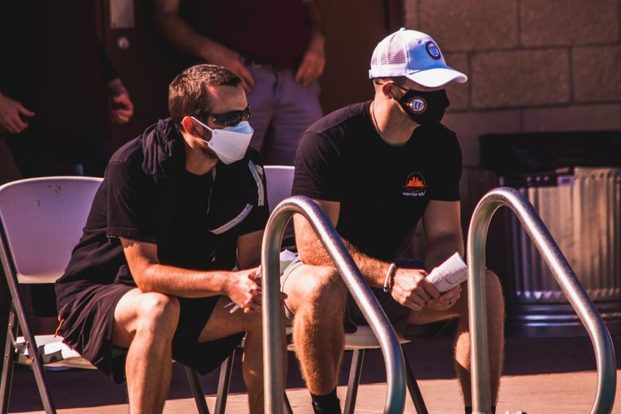 Coaches Matthew McBrearty and Austin Franklin attentively watch the meet. Swimmers talk to McBrearty and Franklin before and after their races for tips.