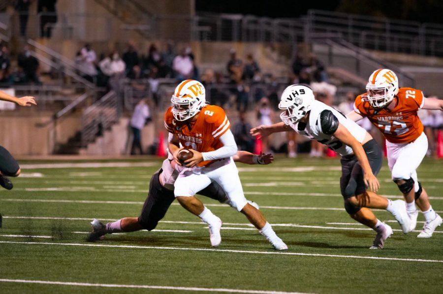 With two defensive players right behind, quarterback RJ Martinez '21 attempts to slip the grip of a defender in last week's game against Vandegrift. Despite Martinez's attempt, he would get taken down moments later.