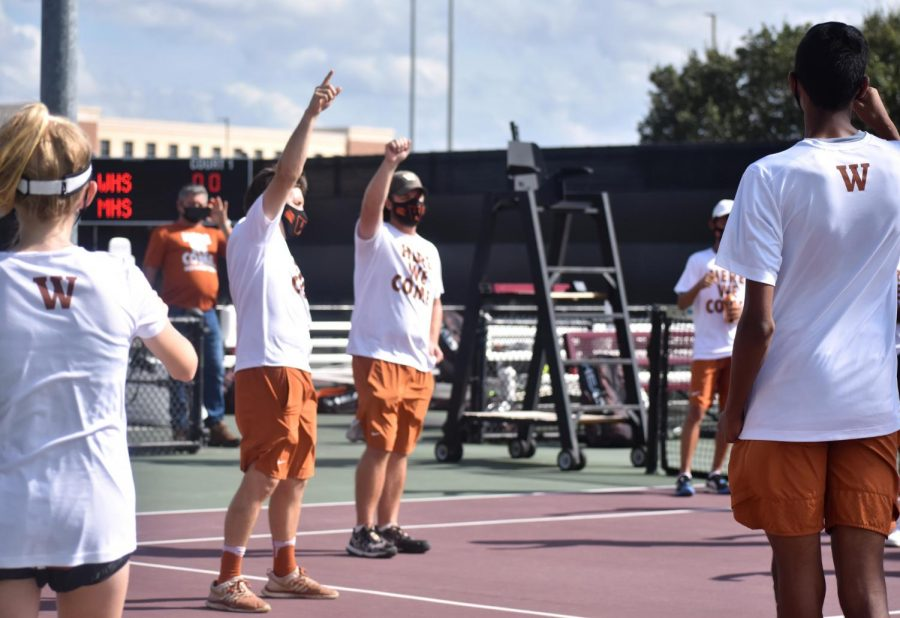 Hands raised high, head coach Travis Dalrymple and assistant coach Daniel Veve lead the varsity tennis team in a pre-match chant before taking on Houston Memorial in the 6A Team Tennis State Semi-Finals. In a high-stakes duel between the top two seeds in the state, Westwood would emerge victorious 10-3.