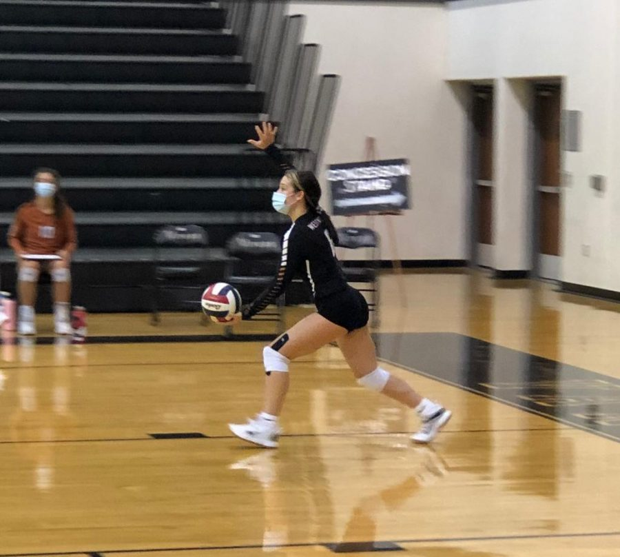 Melani Helms '22 prepares for a serve which ended up in an ace. The opponent team wasn't able to keep the ball in play which resulted immediately in a point for the Westwood orange jv team.