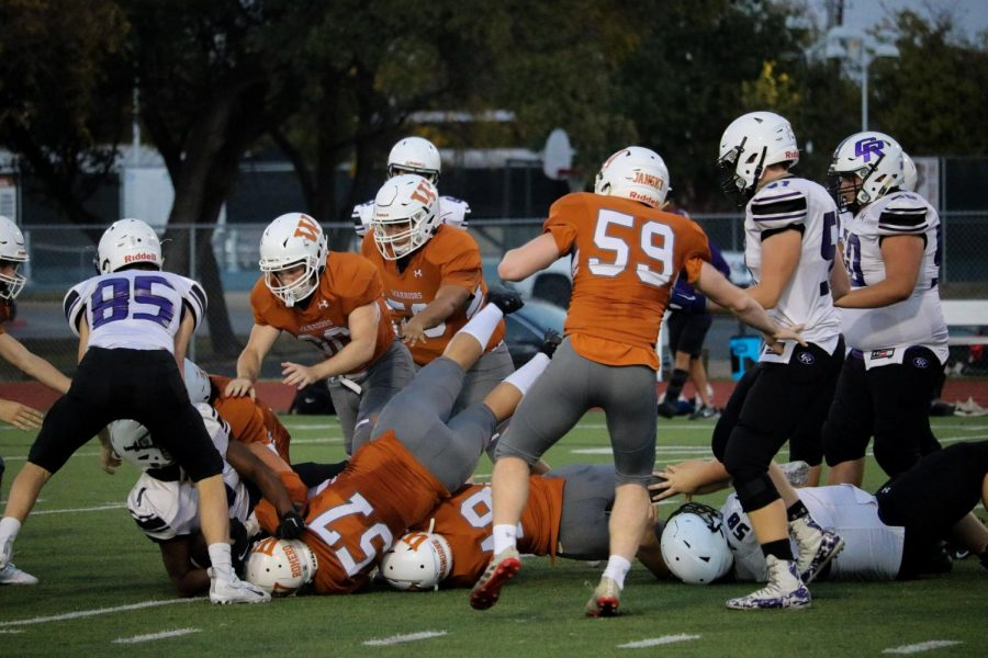 The Warrior defense takes down a Cedar Ridge offensive player. The defense held the play to only a five-yard gain.