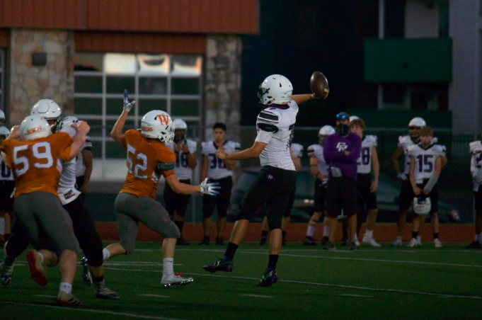 Noah Eisenberg '22 attempts to swat the Cedar Ridge quarterback's pass. He was able to get a hand on the ball and tip it.