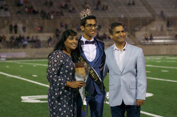 Sohan Agnihotri '21 poses with his parents after being crowned homecoming royalty. He was given a crown, a homecoming royalty sash, and a bouquet of flowers.