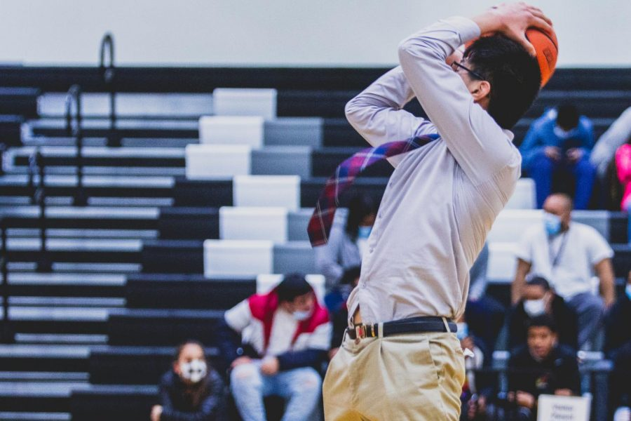 Manager Youngchan Kang ('22) takes to the field during half time, lining up three-pointers. During the game, Kang hypes the audience up to cheer on the basketball team.