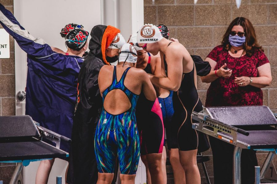 Swimmers Sadie Runeman '21, Shireen Gore '23, Angela Ruan '23, and Ayame Castel '23 partake in their pre-relay tradition of touching fists. The Warriors had a wildly successful district meet.