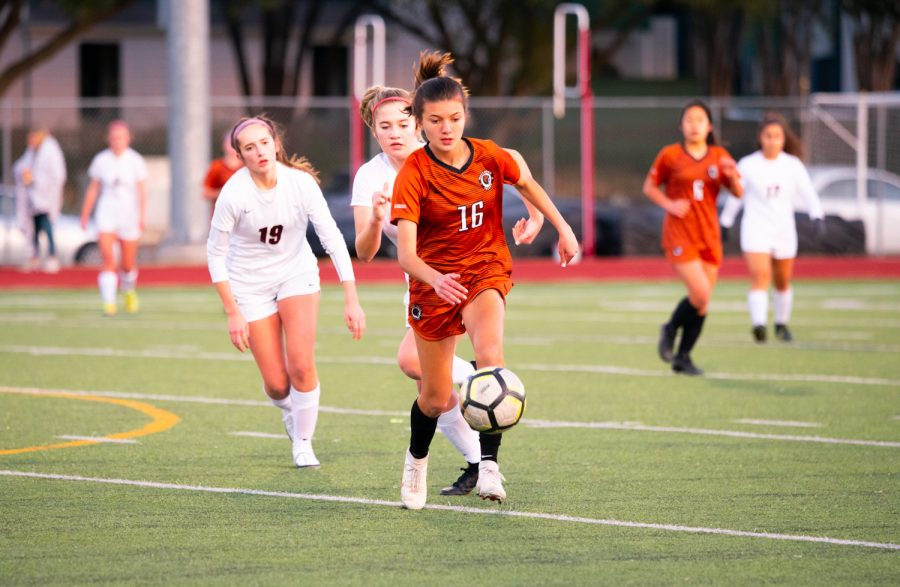 Gaining possession of the ball, forward Katie Forshay '23 dribbles the ball across the field as two opposing defenders run up from behind. Forshay was able to advance the ball downfield.