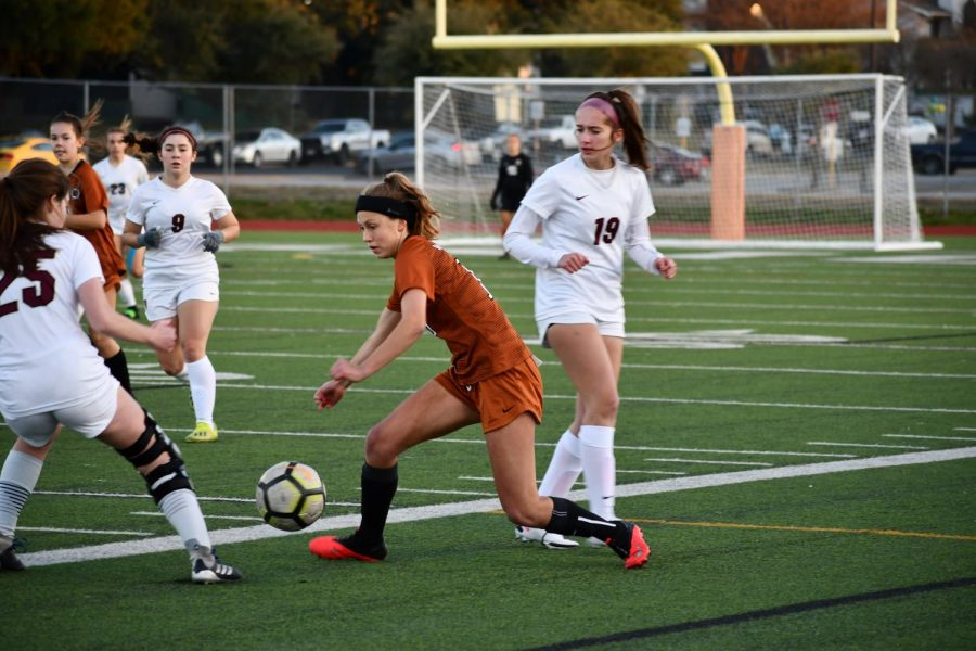 Tayte Webster '23 defends the player with the ball as she runs to attempt to score. She successfully stops the opposing attackers and Westwood regains control.