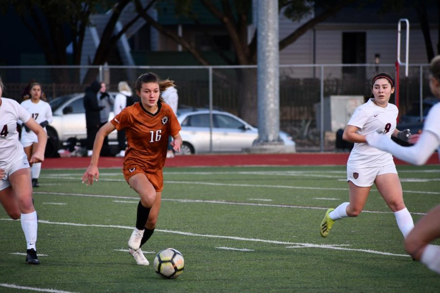 Katie Forshay '23 races to get control of the ball after it was turned lose against Dripping Springs. The Warriors were able to notch a solid win against Vista Ridge in the early goings of district play.