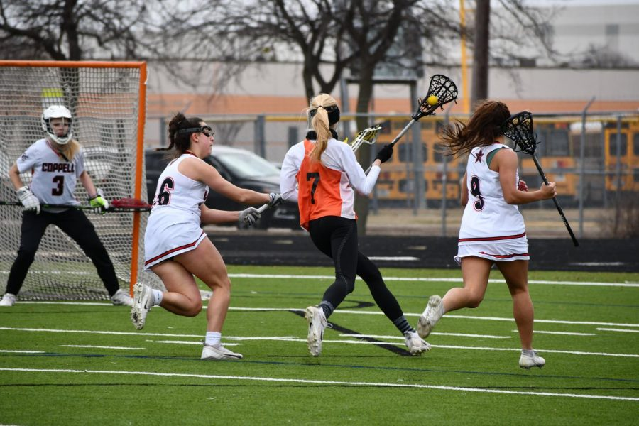 Sprinting towards the goal, Evan Shores '21 takes on two defenders. She successfully gets the ball into the goal.