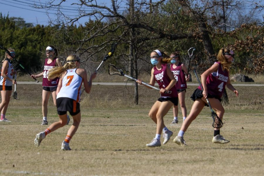 Evan Shores '21 cradles the ball around her Maroon defender. With no clear lane to the goal, she makes a complete pass to Laura Moravec '22.