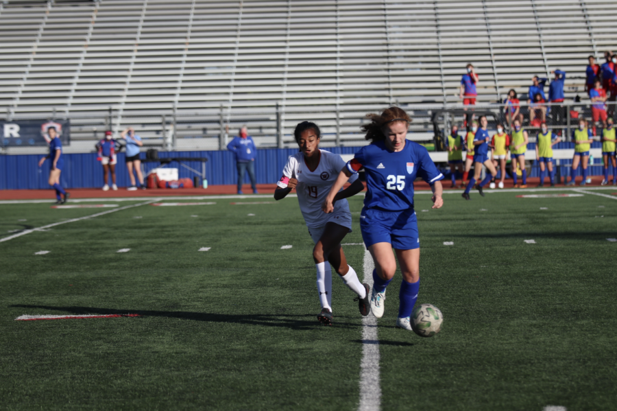 Deepti Choudhury 21 catches up to her opponent with the ball. She is able to gain possession and make a quick pass to her teammates.