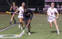 Defender Kaybee Briggs '21 scoops up a ground ball before the Austin attackers. She then ran the ball down the midfield to make a pass.