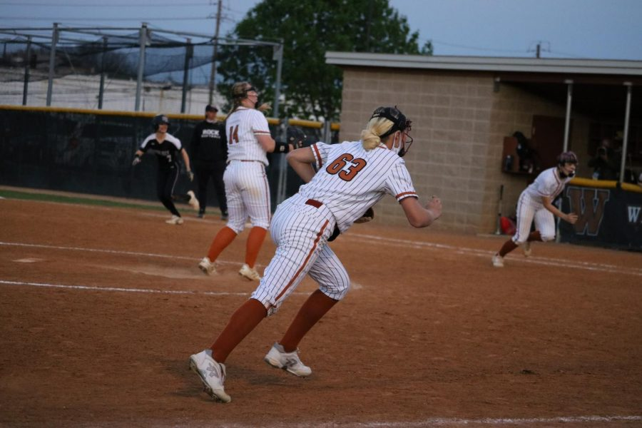 Center fielder Dorothy Ziebell '24  runs to catch the ball hit by the offensive team.  The batter had reached the first base before the fielders could catch the ball.