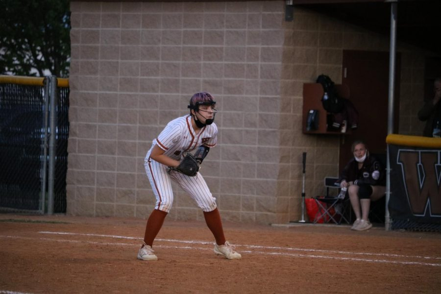 First baseman Kylie Wardlow '23 is standing on the first base. Wardlow was waiting to catch the ball that flies out of the infield.