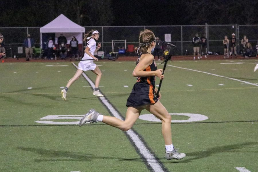 Bridgette Moravec '24 brings the ball to the attackers from the opposing side. She was able to outrun her defenders and settle the ball so the Warriors could make a goal.