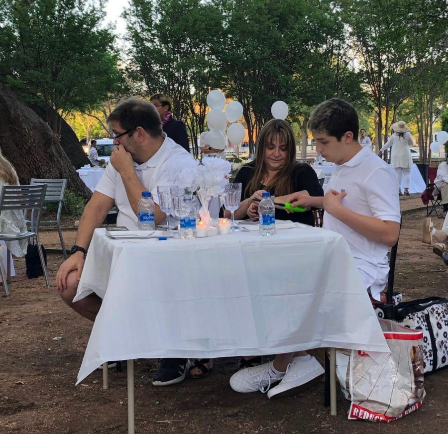 Matthew Allen '23 and his family sitting at their own picnic table listening to the senior speeches. Allen '23 and his family brought their own food so they could enjoy it during the event.