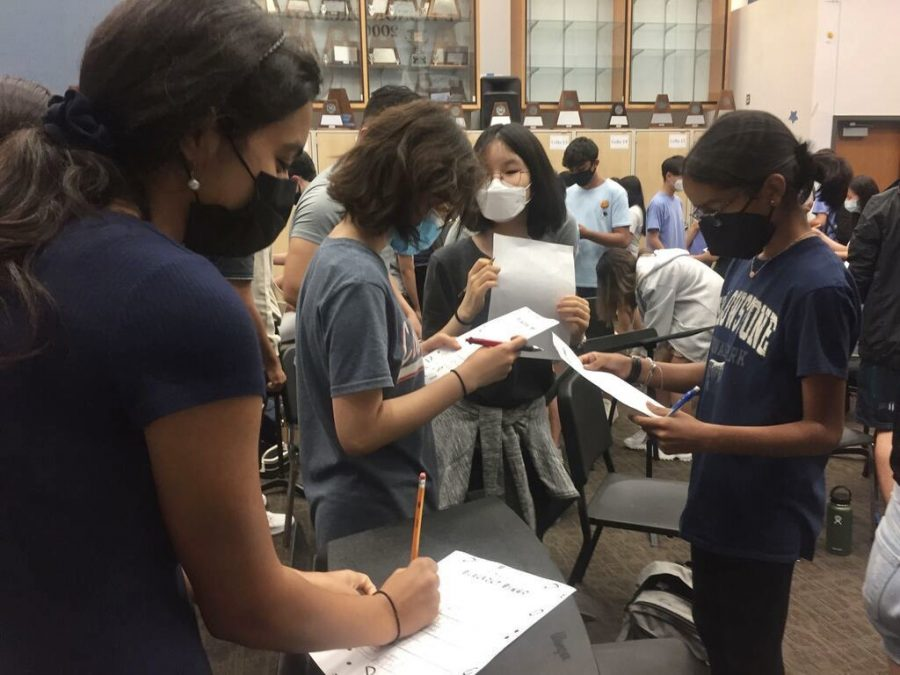Symphony orchestra students Serena Manwani 22, Grace Huh 25, and Sanjana Alluri 25 exchange blackout bingo sheets during day two of Welcome Week.