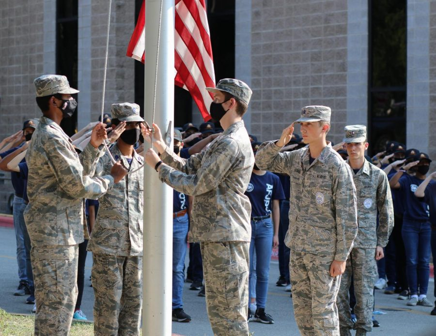 With cadets saluting in the background, Inesh Nambiar 23, Nolan James Sedillo '22, and Vikranth Srinivasan Ragavan '22 hoist the flag for JROTCs 9/11 memorial ceremony. The memorial was hosted to commemorate the lives lost in the infamous terrorist attacks all over the US 20 years ago.