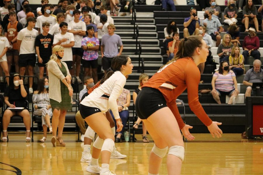 Number eight, Erin Fagan 22, squats ready beside teammate Lola Fernandez 23, awaiting a  serve. The two wore focused looks.