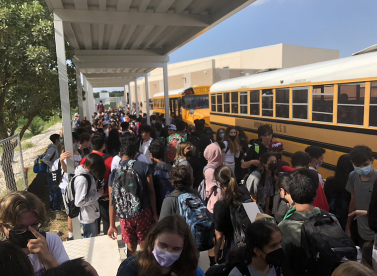 Students wait for the buses underneath the new canopy.