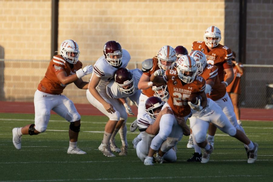 Running back Brian Lee 22 gets past several defenders while his teammates help. Lee has been an important player for the Warriors, with 102 yards last season.