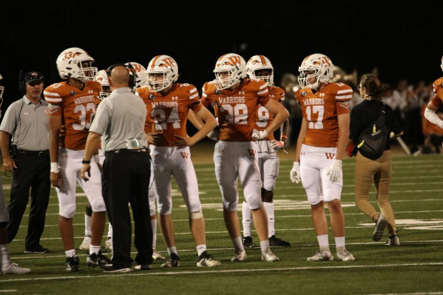 From left to right, Adi Jandhyala 22, Hayden Schultz 23, Carter Waghorne 22, Jaiden Webber 23, and Jackson Laughlin 23 stand in front of their coach to discuss the next play. The Warriors were on their third down.