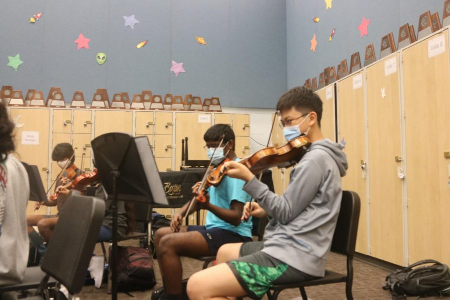 Alfred Nonis 23 and Andrew Seo 23 play during Orchestra class. The viola section has a solo in the Moorside Suite piece.