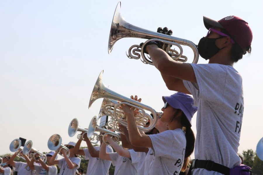 """With other mellophones beside him in a concert arc, section leader Ian Kim '22 quickly gets set to warm up at the beginning of rehearsal on Friday, Sept. 10. Though the non-competitive marching season in 2020 was difficult, it inspired him to become an example for his peers this year. """"It's my duty to help the underclassmen appreciate band the way that I appreciate it,"""" Kim said."""