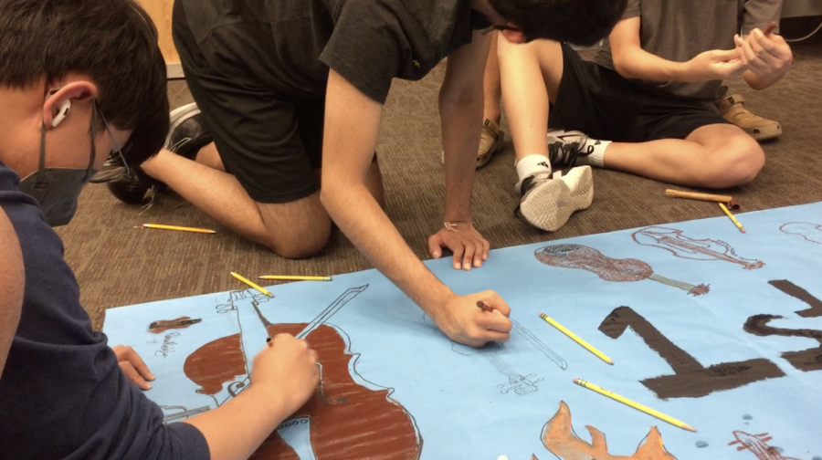Alex Kim 23 and fellow first violinists decorate their section poster. The first violin poster featured various violins drawn by each of the members.