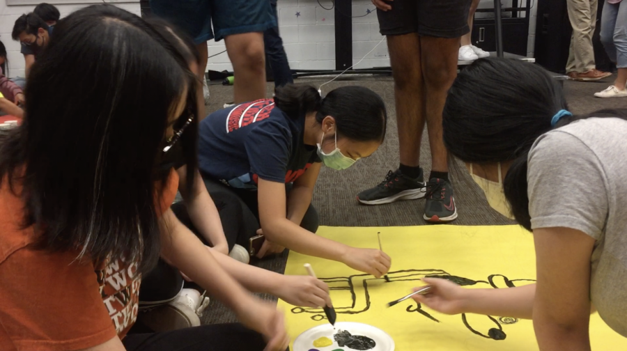 Soohyun Ahn 24, Allison Yao 25, and fellow violists decorate their section poster