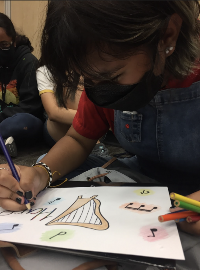 Izzy Valenzuela 24 creates her harp section poster.