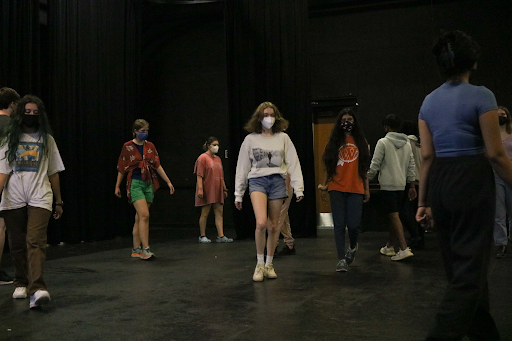 Students practice showing emotion through their movements in the theatre room. Ms. Lydia Coats, theatre director, gives directions about different emotions and movements to portray as students walk around the room trying them out.