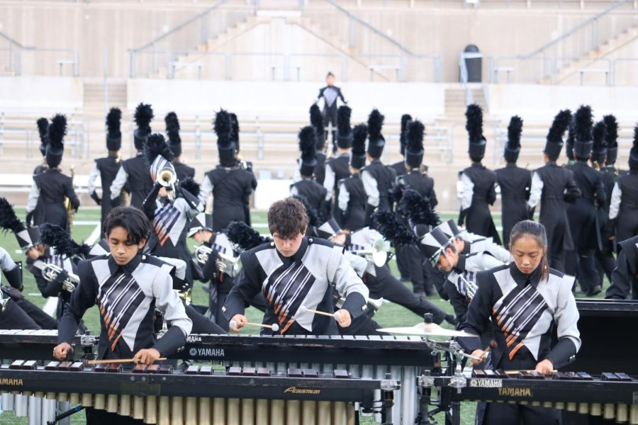 """Neel Kotichintala 25, Pierce Williams '22, and Caroline Zhuang '23 play the marimba in the front. The percussion were in the front while everyone moved around behind them.""""[Playing percussion] is really interesting because you kind of get a perspective that the winds don't,"""" Williams said. """"As percussionists, you're much more concerned with the rhythm of the show, and you're always trying to keep tempo. The winds kind of rely on you to keep the tempo while they do whatever else they do."""